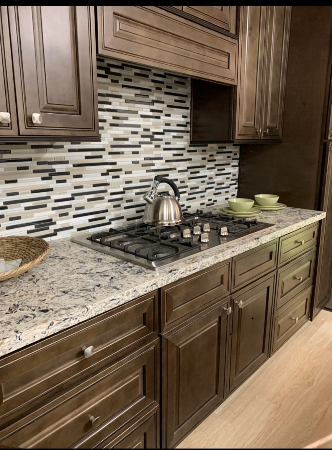 Brown cabinets with gray tile backsplash